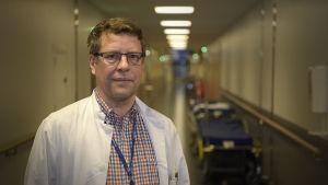 En man med läkarrock ser mot kameran i en sjukhuskorridor