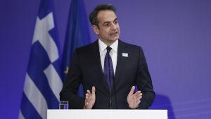 Greklands premiärminister Kyriakos Mitsotakis håller tar vid ett podium. Bakom honom ser man en EU-flagga och Greklands flagga.