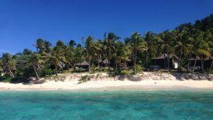 Klarblått vatten och vit sand för besökaren in mot paradisön Matamanoa med bungalower och palmer.