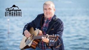 Tom Håkans spelar gitarr vid havet.