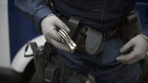 Polis håller i handklovar.