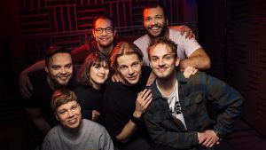 Dingon ääninäyttelijät vierekkäin kasassa äänitysstudion punaisen valon kajastuksessa.