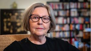 Anja Lahtinen hemma, i svart klänning med bokhylla i bakgrunden.