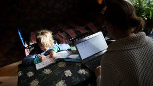 En pojke sitter och gör skolarbete vid ett bord. På andra sidan bordet sitter en kvinna och jobbar på en bärbar dator.