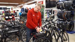 Polkupyörien myyjä polkupyörien äärellä