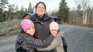 En mamma som omfamnas av sina två döttrar.