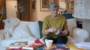 Margita Vainio sitter i en soffa med en hel hop med böcker framför sig