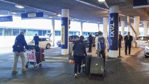 taxibilar på Helsingfors-Vanda flygplats. I förgrunden passagerare som promenerar fram till bilarna.