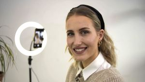 kvinna med hårband ler mot kameran