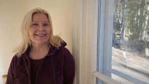 Blond kvinna poserar vid ett fönster.
