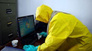 suojapukuinen mies puhdistaa tietokonetta