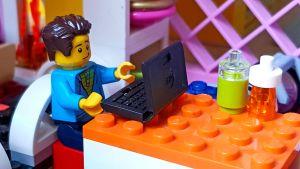 legoukko istuu pienen legotietokoneen ääressä