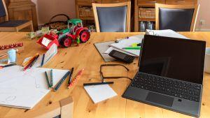Pöydällä on kannettava tietokone ja mm. kyniä, kännykkä ja leikkitraktori.