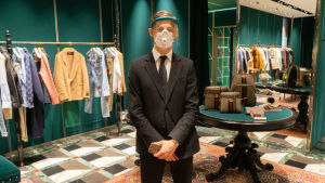 Man in gucci clothing shop with mask