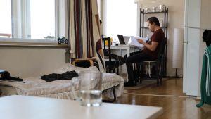 En lägenhet med en person som sitter i bakgrunden och studerar.