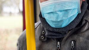 Man i bussen bär ansiktsskydd