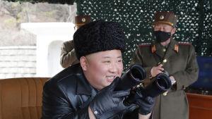 Officerare i närheten av Kim Jong-Un bar ansiktsmasker på bilder som är daterade den 3 mars.