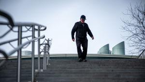 Mies kävelee portaita alas.