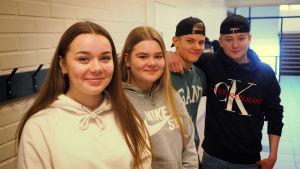 Fyra niondeklassare under en rast i korridoren i Ådalens skola i Kronoby. Två tjejer som har långt hår och två killar som har keps.