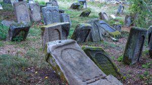 Hautausmaalla on vanhoja, osittain kaatuneita hautakiviä.