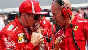 Kimi Räikkönen dricker ur en flaska och talar med Mark Arnall.
