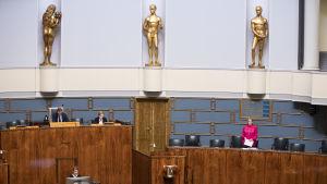 Riksdagen håller sociala avstånd. Talmannen, en minister och några ledamöter på plats i plenum