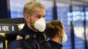 En polis i uniform med ett vitt andningsskydd för mun och näsa.