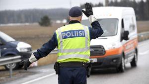 En polis fotograferad bakifrån står och dirigerar trafik vid en väg.