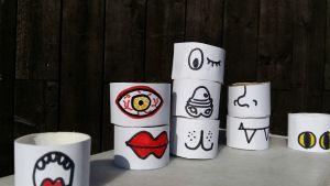 Ett pussel av tomma toalettpappersrullar. På varje del är det målat en del av ett ansikte. Ögon, näsor och munnar i olika varianter. En del av bitarna är staplade på varandra.