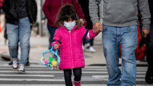 Ung flicka bär ansiktsmask i Queens, New York.