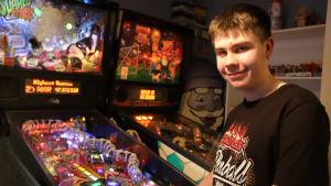 16-vuotias poika poseeraa flipperikoneiden vieressä