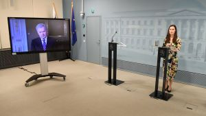 Sanna Marin vid ett podium, president Sauli Niinistö på en stor tv-skärm.