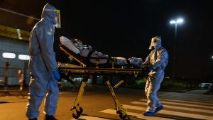 Två hälsovårdare rullar en sjuk äldre kvinna på en bår mot en ambulans. Det är natt och vårdare är klädda i heltäckande skyddsutrustning.