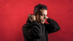 Pääosanesittäjä Rami Malek seisoo punaista taustaa vasten ja on laittamassa hupparin huppua päähänsä.