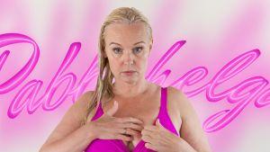 Vaaleatukkainen, keski-ikää lähestyvä nainen asettaa fuksianvärisiä rintaliivejään.