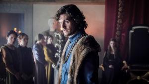 Lorenzo de' Medici (näyttelijä Daniel Sharman) seisoo kuvan etualalla ilmeisesti linnan sisätiloissa.