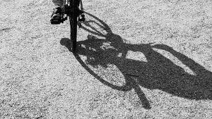 En fot som trampar en cykel över grus och cykelns skugga är enorm på grusplanen.