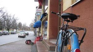 En gata med några parkerade rollatorer och en cykel utanför en dagcentral.