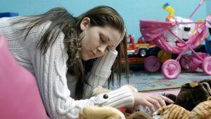 Väsynyt äiti nuokkuu lastenhuoneen lattialla.