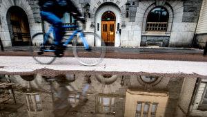 En cyklist cyklar invid en stor vattenpöl i Åbo.