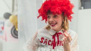 Nuori nainen (näyttelijä Anna Airola) vappuperuukki päässään.