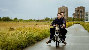 Kaksi miestä ajaa iloisena mopolla, ilman kypäriä, taustalla kerrostalolähiö.
