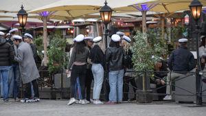 Unga med studentmössor samlas på och omkring uteservering i Stockholm.