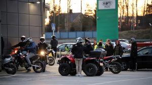 Ungdomar står med mopeder och fyrhjulingar på en parkering i kvällsljus.
