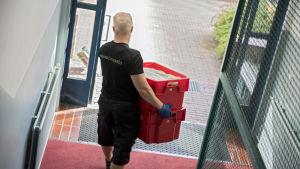 en person flyttar något i en stor plastlåda