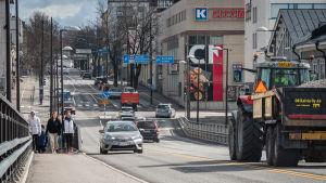 Traktor och bilar kör längs gata i staden
