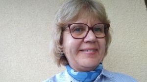 En kvinna med ljust hår och glasögon ler.