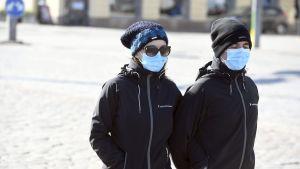 Två personer iförda ansiktsskydd promenerar på salutorget i Helsingfors på valborgsmässoafton 2020.