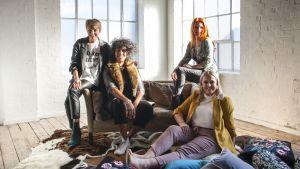 Neljä noin 35-45-vuotiasta naista istuu sohvalla ja lattialla vaaleassa asunossa.