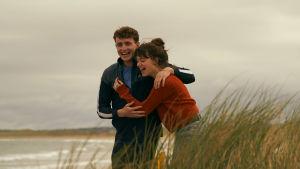 Nuori pariskunta, mies ja nainen, kävelee rannalla lähekkäin ja nauraa.